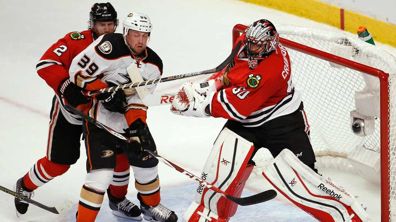 Chicago Blackhawks goalie Corey Crawford (50) hits Anaheim Ducks Matt Beleskey (39) with his stick as defenseman Duncan Keith (2) watches during Game 4 on May 23, 2015, in Chicago