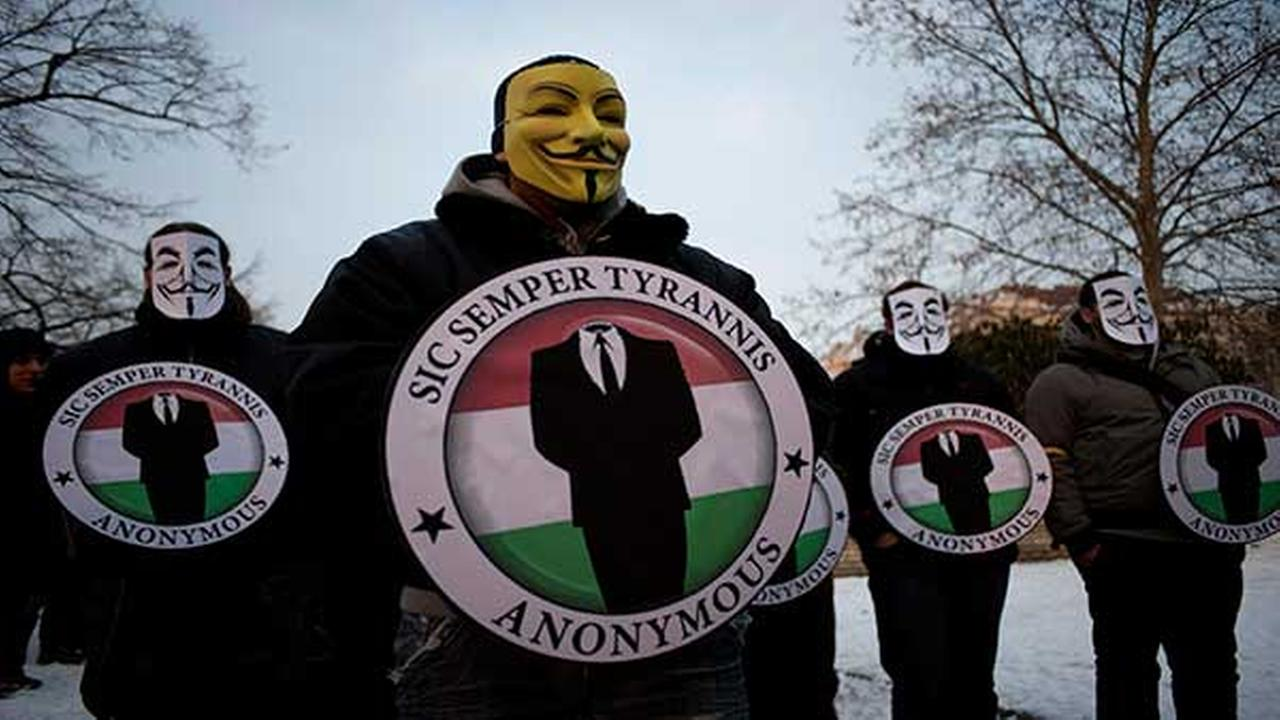 Protestors wearing Guy Fawks masks hold the logos of the international hacker group Anonymous during a demonstration against ACTA in Budapest, Hungary on Feb. 11, 2012.