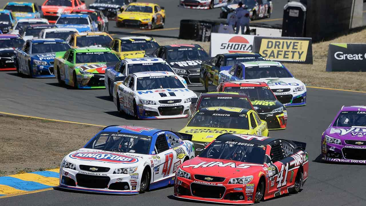 A.J. Allmendinger (47) and Kurt Busch (41) make their through Turn 2 at the start of the NASCAR Sprint Cup Series auto race on June 28, 2015, in Sonoma, Calif.