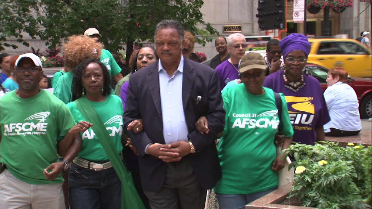 Reverend Jesse Jackson marches Saturday at the Thompson Center against proposed budget cuts.