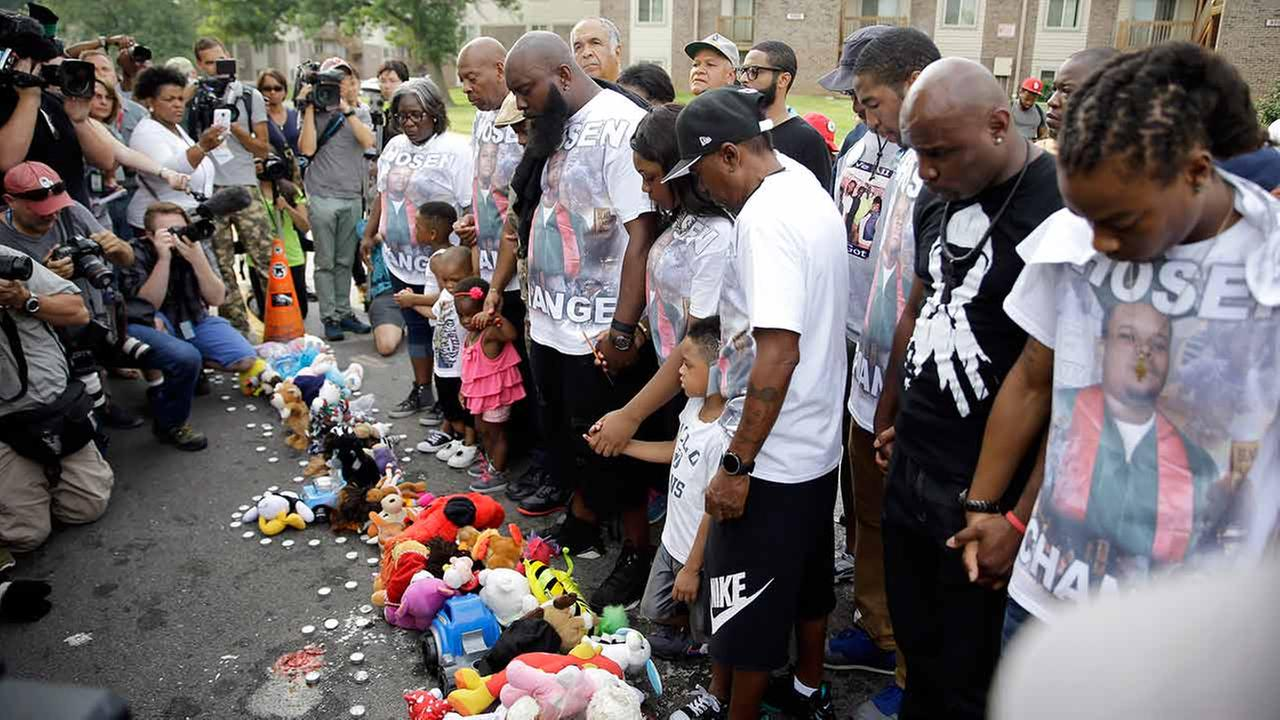Michael Brown Sr. along with family and friends stop to pray at a memorial to Browns son before taking part in a parade in his sons honor on Aug. 8, 2015, in Ferguson, Mo.