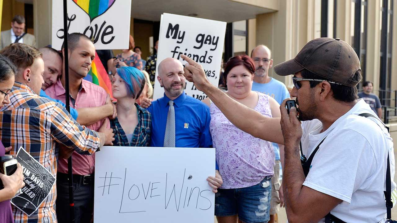 Edgar Orea, right, preaches to a group of same sex marriage supporters that have gathered outside the Carl D. Perkins Federal Building in Ashland, Ky.