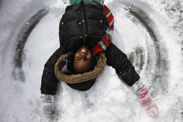 "<div class=""meta image-caption""><div class=""origin-logo origin-image ap""><span>AP</span></div><span class=""caption-text"">Jamilya Rich, 10, of Washington, makes a snow angel by the sidewalk in Washington, on Monday, March 2, 2009. ((AP Photo/Jacquelyn Martin))</span></div>"