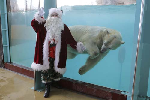 <div class='meta'><div class='origin-logo' data-origin='none'></div><span class='caption-text' data-credit='AP Photo/Lionel Cironneau'>A man dressed in a Santa Claus costume poses for photographers with a polar bear named &#34;Raspoutine&#34;, at the animal exhibition park Marineland in Antibes, southern France.</span></div>
