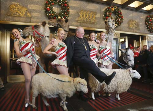 <div class='meta'><div class='origin-logo' data-origin='none'></div><span class='caption-text' data-credit='AP Photo/Bebeto Matthews'>Cardinal Timothy Dolan, center, kicks his leg as he poses with members of the Radio City Rockettes, after he blessed camels, sheep and a donkey,  in New York.</span></div>