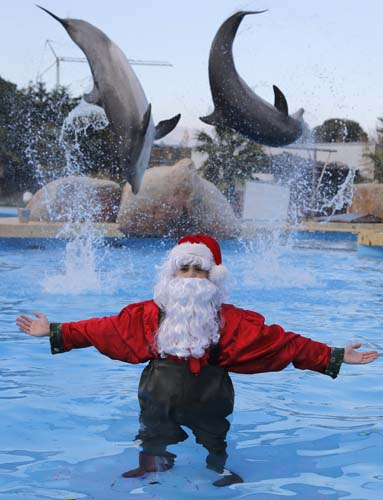 <div class='meta'><div class='origin-logo' data-origin='none'></div><span class='caption-text' data-credit='AP Photo/Lionel Cironneau'>A man dressed as Santa Claus poses for photographers with two dolphins, at the Marineland animal exhibition park in Antibes, southeastern France.</span></div>