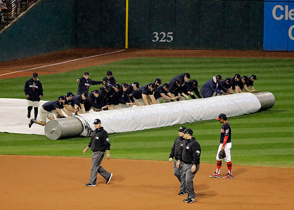 <div class='meta'><div class='origin-logo' data-origin='none'></div><span class='caption-text' data-credit='AP Photo/Gene J. Puskar'>Workers cover the infield at Progressive Field during the 10th inning of Game 7.</span></div>