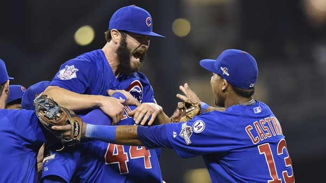 Chicago Cubs first baseman Anthony Rizzo, (44), holds Chicago Cubs starting pitcher Jake Arrieta as shortstop Starlin Castro (13) joins in the celebration after they defeated the Pittsburgh Pirates in the NL wild-card game.
