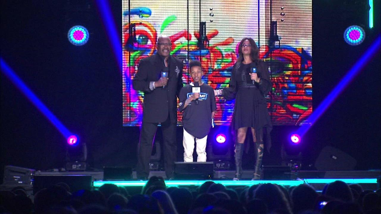 Kipp Elementary School student Guyshon Moore joined Cheryl and Hosea Sanders on stage at WE Day in Allstate Arena.