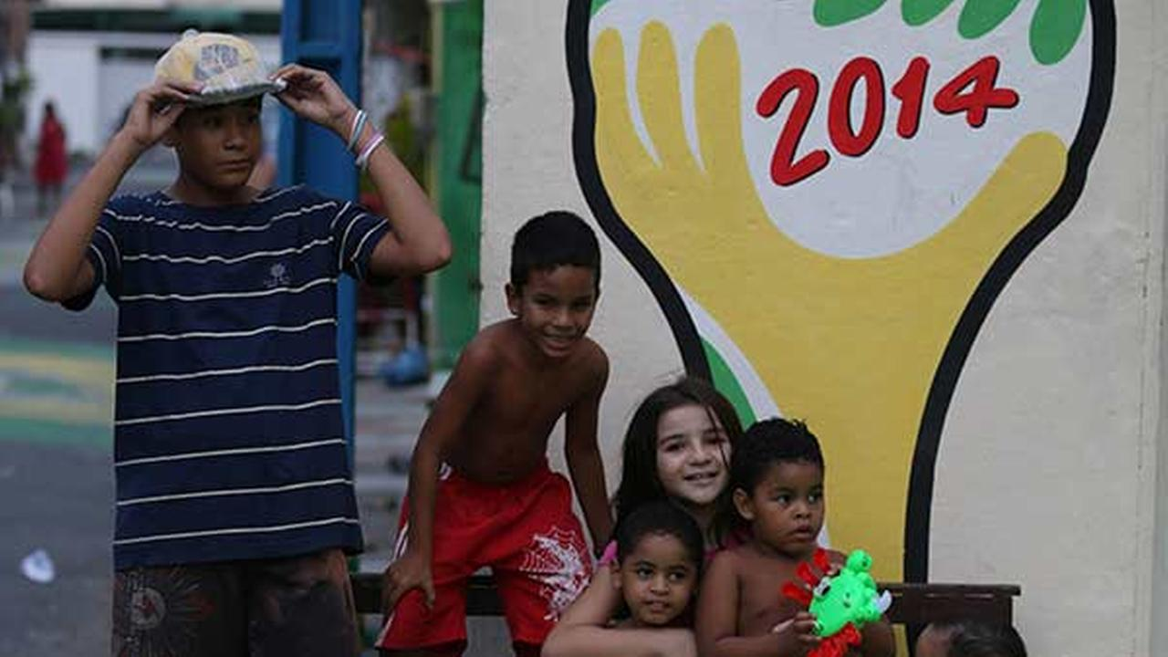 Children huddle in front of the 2014 soccer World Cup logo in Fortaleza, Brazil AP Photo/ Martin Mejia