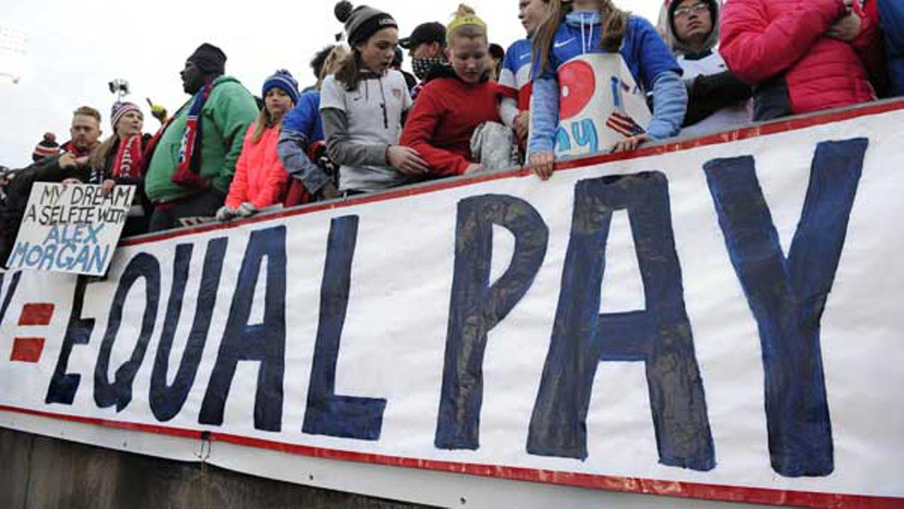 Fans stand behind a large sign for equal pay for the womens soccer team during an international friendly soccer match between the United States and Colombia.