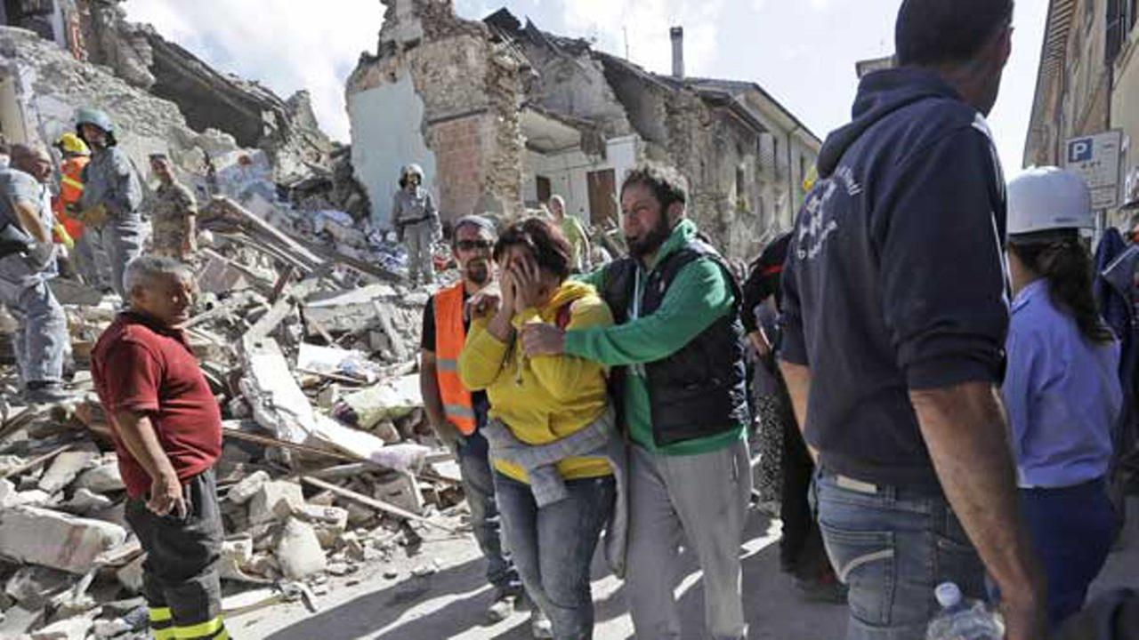 A woman is comforted as she walks through rubble after an earthquake, in Amatrice, central Italy.