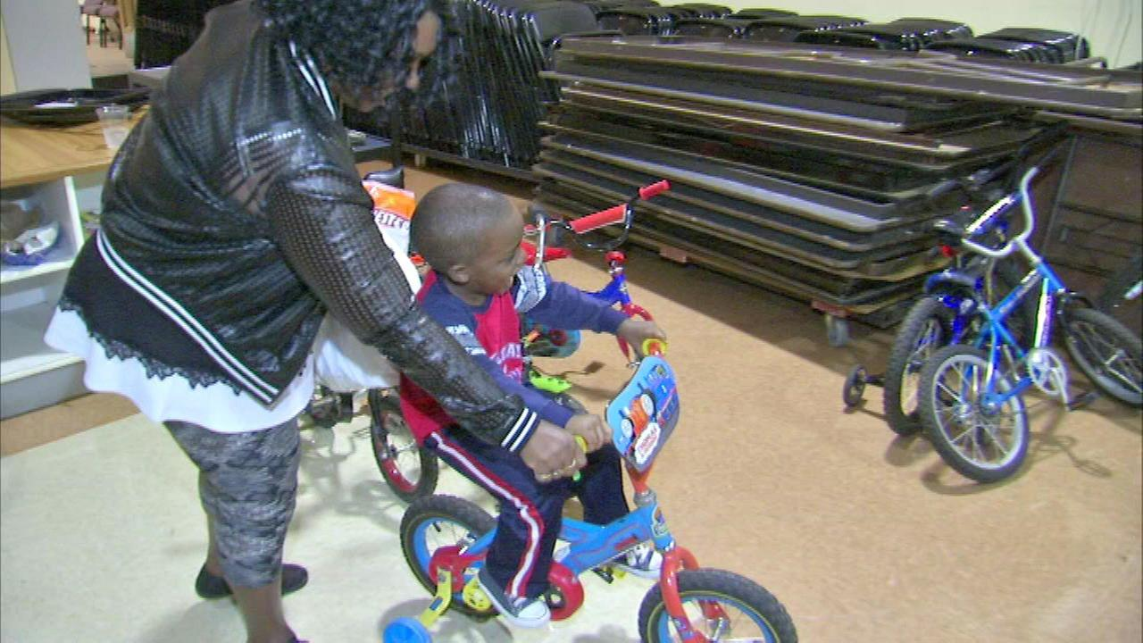 A kid gets a new bike after Saint Sabina Church partnered with Working Bikes  for a giveaway.