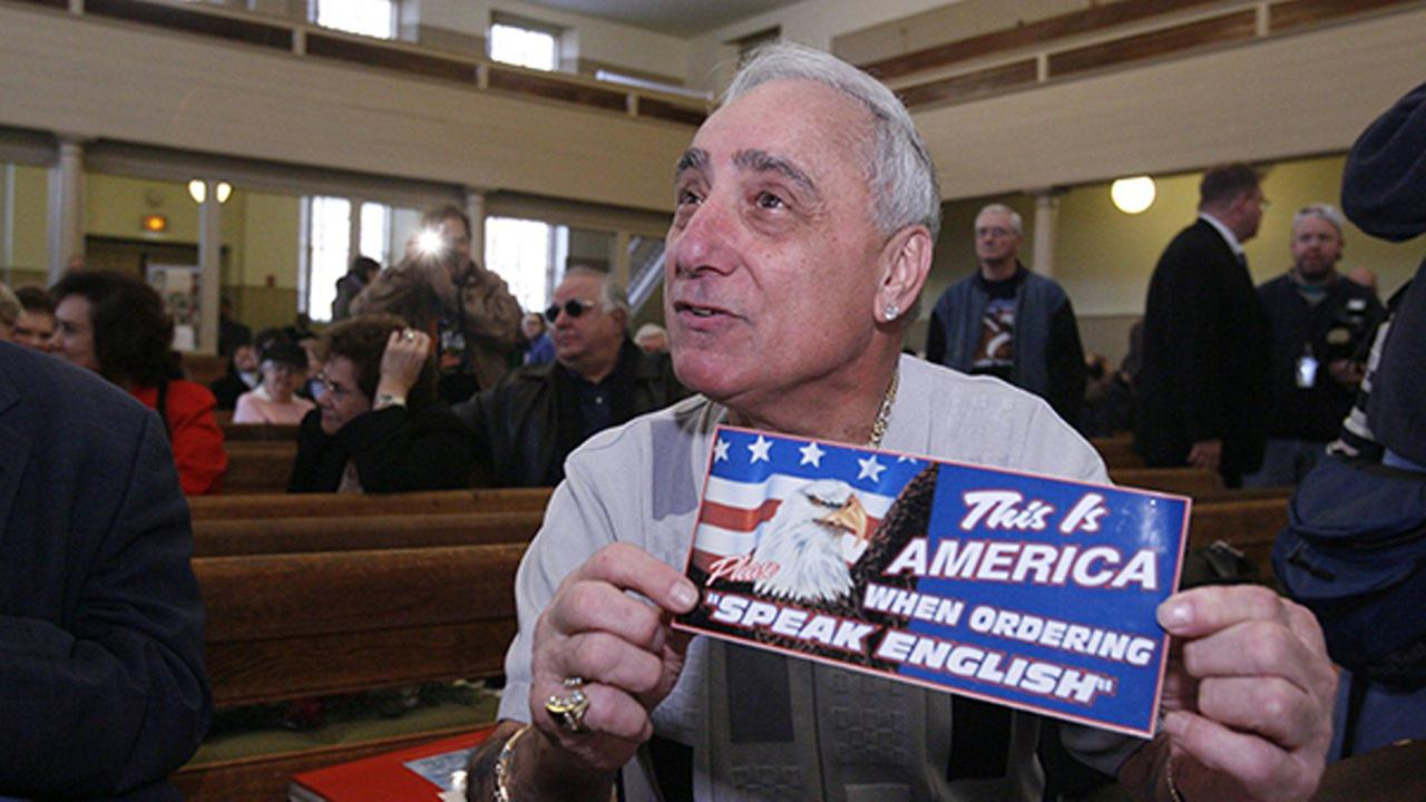In this Dec. 14, 2007, file photo, Joseph Vento, owner of Genos Steaks in Philadelphia, displays a sign that was displayed at his restaurant.