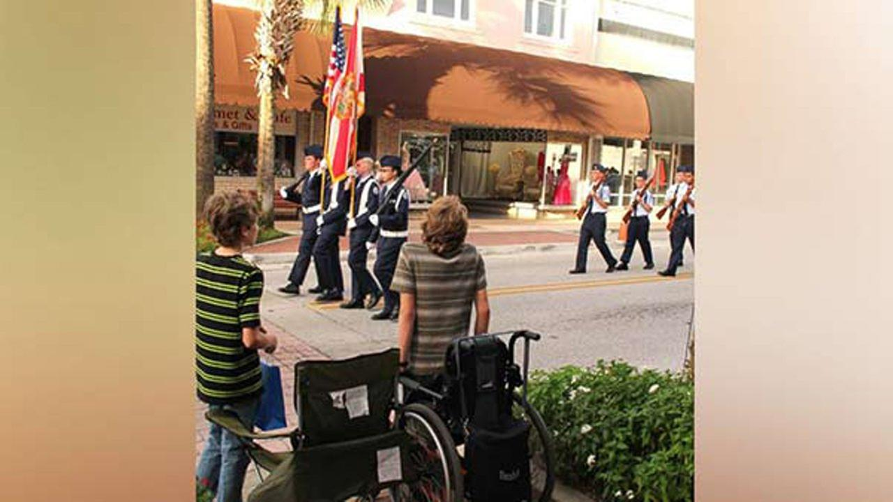 Arek Trenholm is wheelchair-bound but hoisted himself up to stand for the American flag.