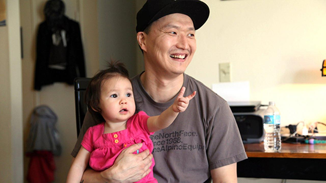 FILE - Korean adoptee Adam Crapser poses with daughter, Christal, 1, in the familys living room. Crapsers adoptive parents neglected to make him a U.S. citizen.