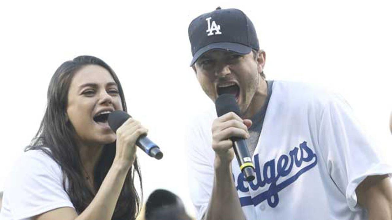 Ashton Kutcher and wife Mila Kunis announce the starting lineup before Game 4 of the National League championship series between the Chicago Cubs and the Los Angeles Dodgers.
