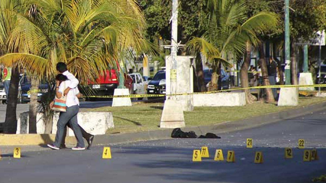 A couple walks past markers placed where bullet casings were found by investigators near the state prosecutors office after gunmen opened fire on the building in Cancun, Mexico.