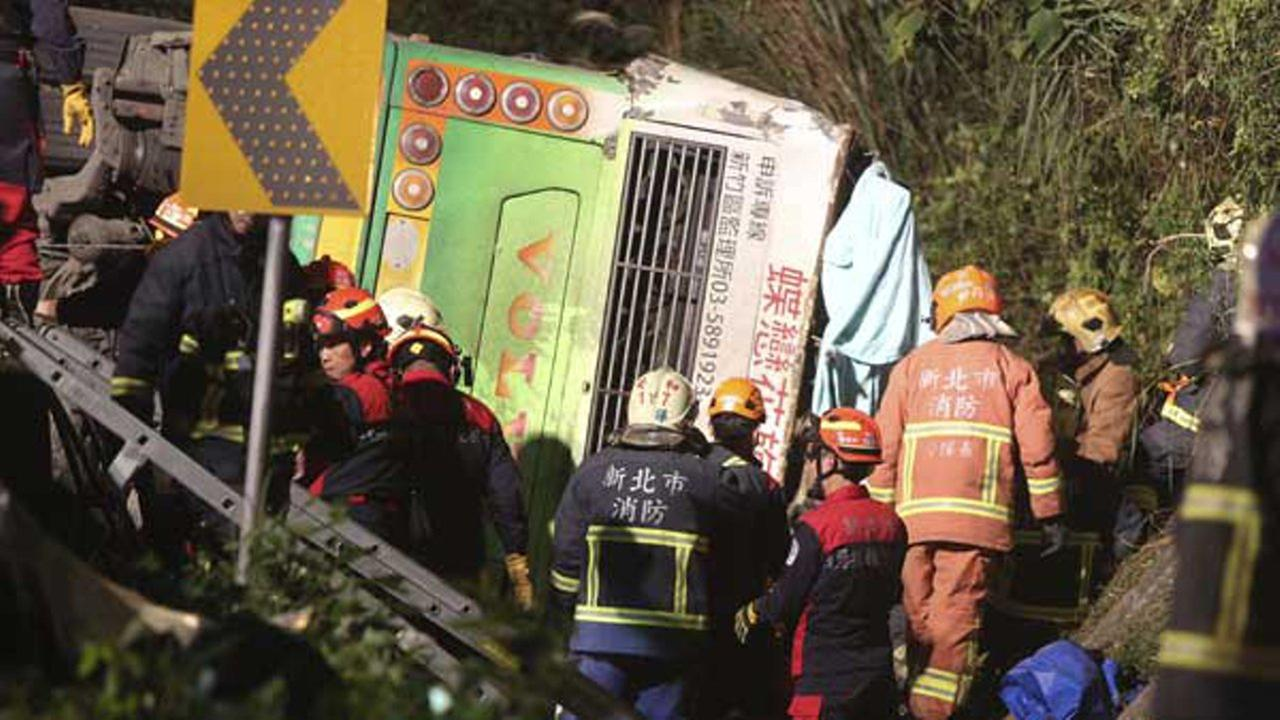 Members of rescue team at the scene where a bus collided with a car on a highway in Taipei, Taiwan, Monday, Feb. 13, 2017.