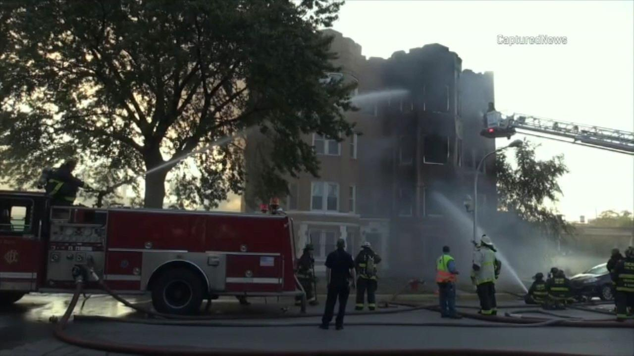 Firefighters battle a two-alarm fire at a Washington Park apartment building Saturday morning.