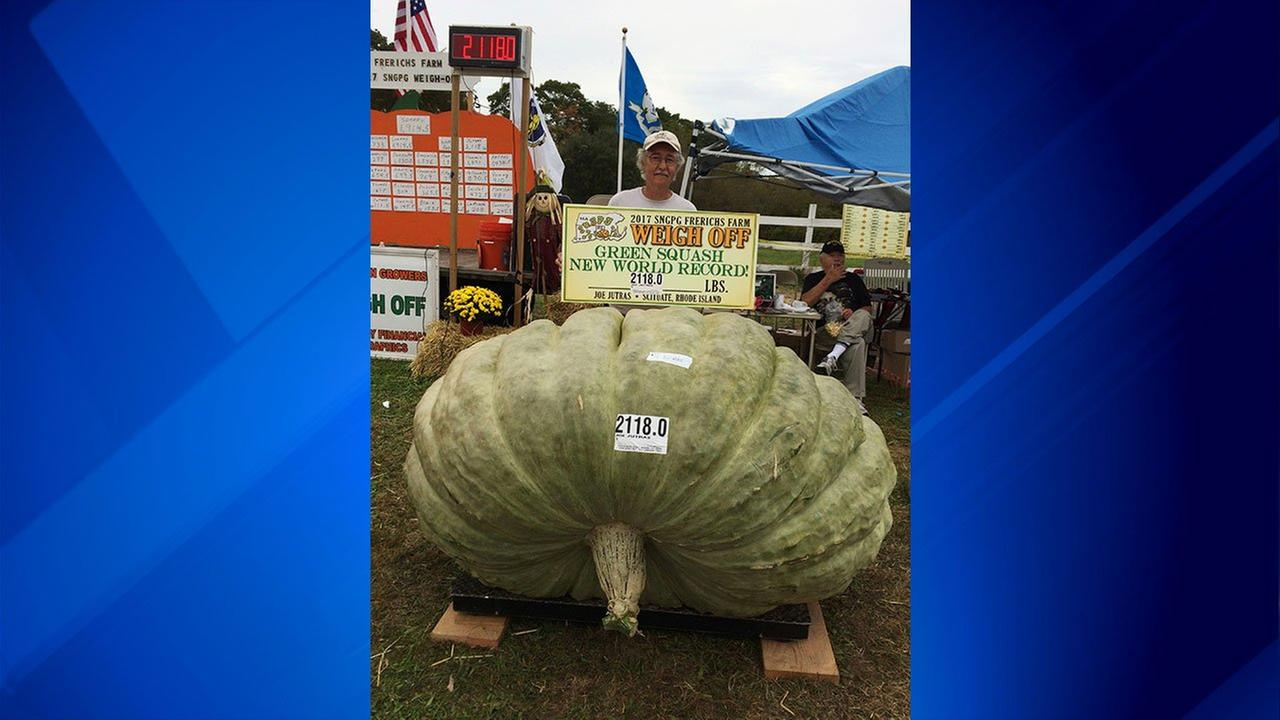 In this Oct. 7, 2017, photo provided by Susan Jutras, Joe Jutras stands with his world record breaking, 2,118-pound squash, following a weigh-in at Frerichs Farm in Warren, R.I.