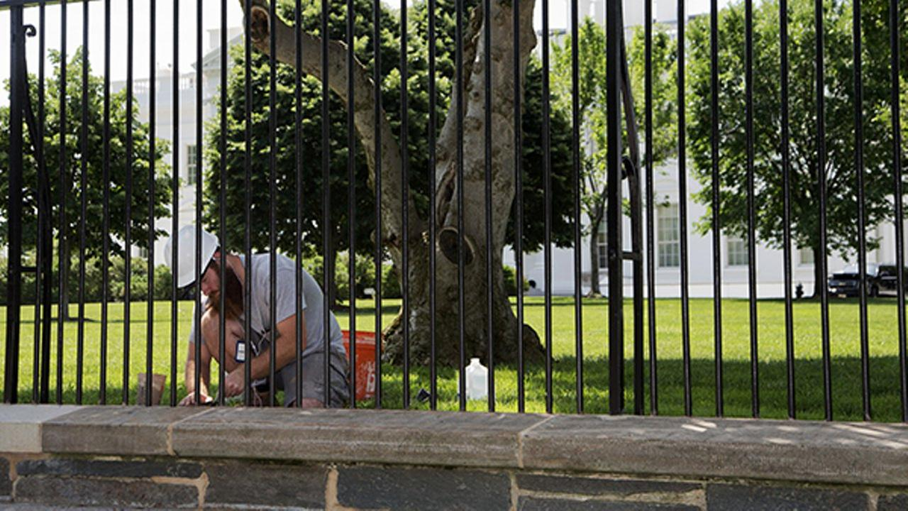 File: A worker works on the White House fence on the North Lawn in Washington, Thursday, May 28, 2015.