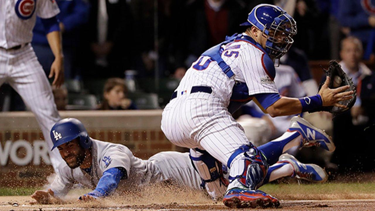 Los Angeles Dodgers Chris Taylor slides safely into home plate against Chicago Cubs catcher Willson Contreras during the first inning of Game 5 of the NLCS.