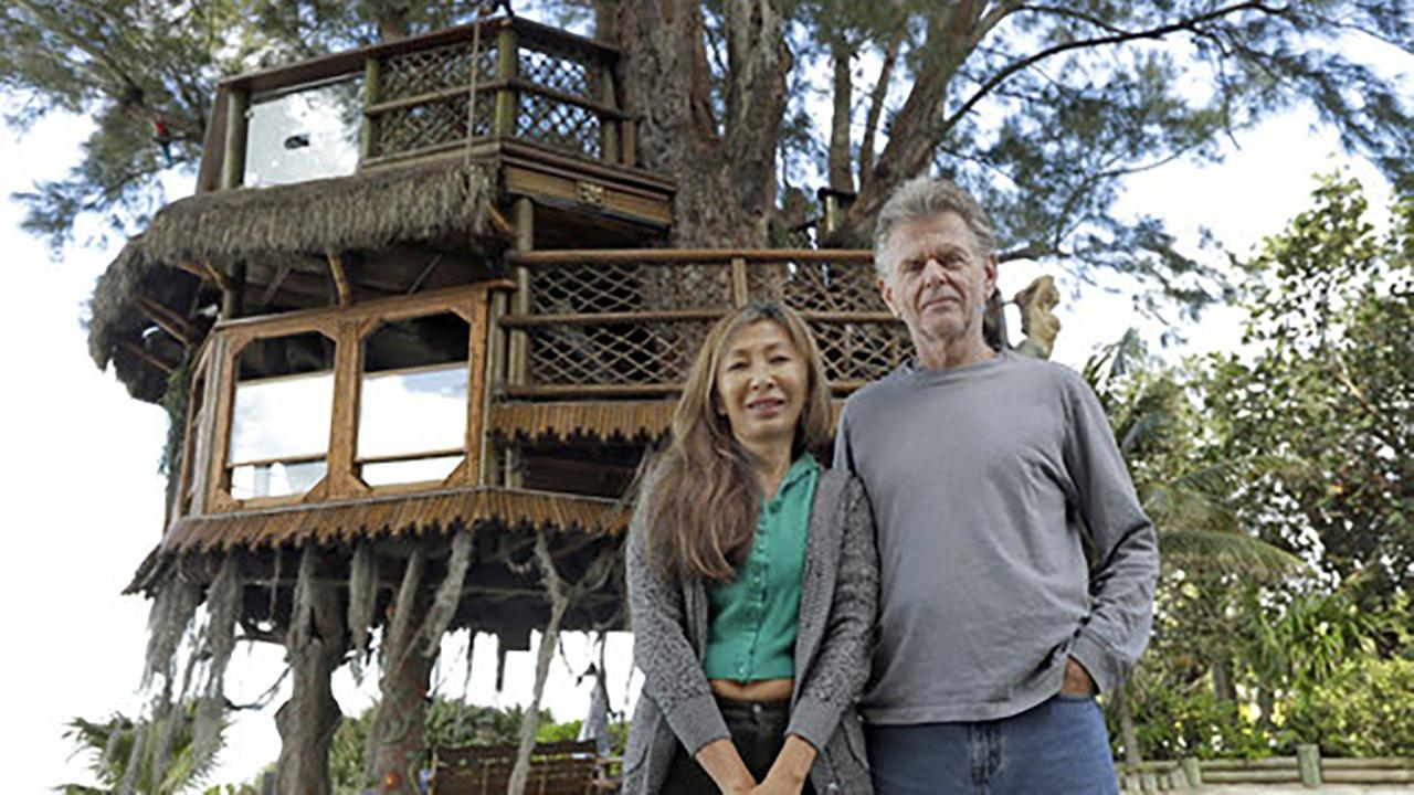 Lynn Tran and her husband Richard Hazen pose near their Australian pine treehouse Thursday, Jan. 4, 2018, in Holmes Beach, Fla.