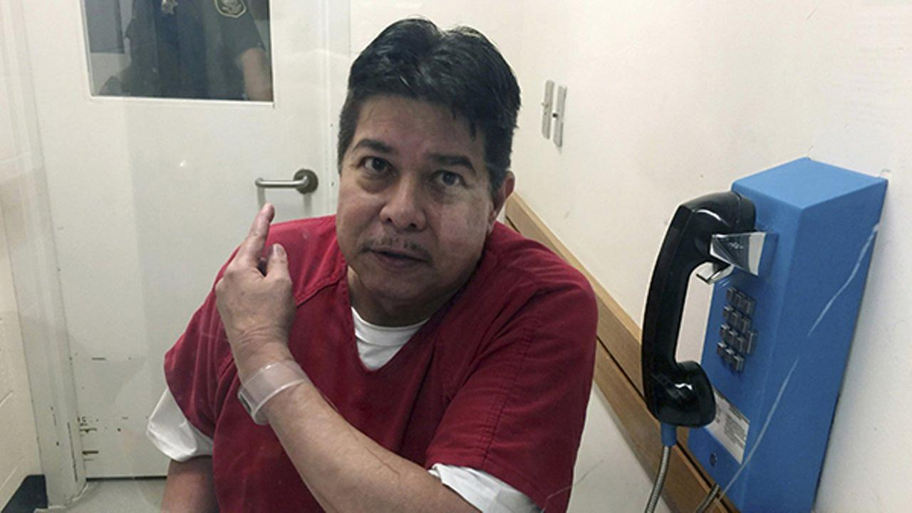 In this Nov. 17, 2017, file photo, escaped hospital patient Randall Saito points to a guard as he sits in an inmate visitors booth at San Joaquin County Jail.