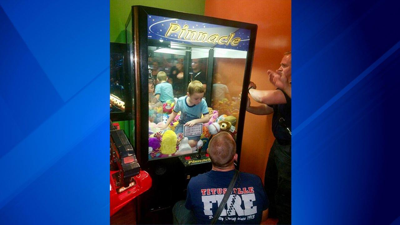 Boy seeking toy climbs into arcade claw machine. Firefighters save the day