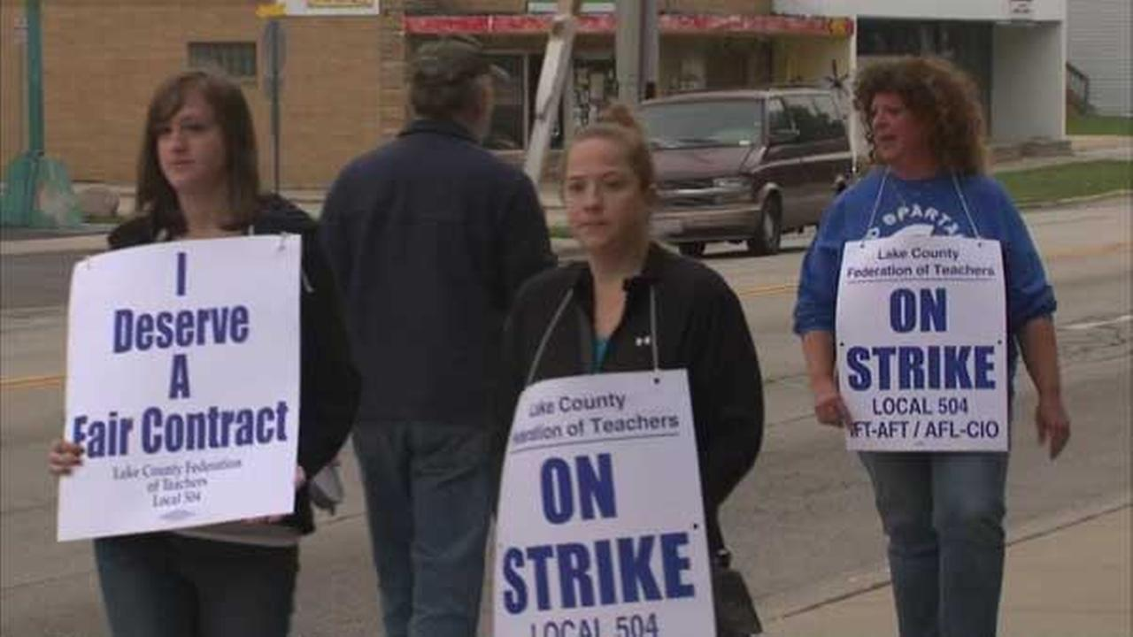 Striking teachers picket outside Waukegan East High School as contract negotiations continue.