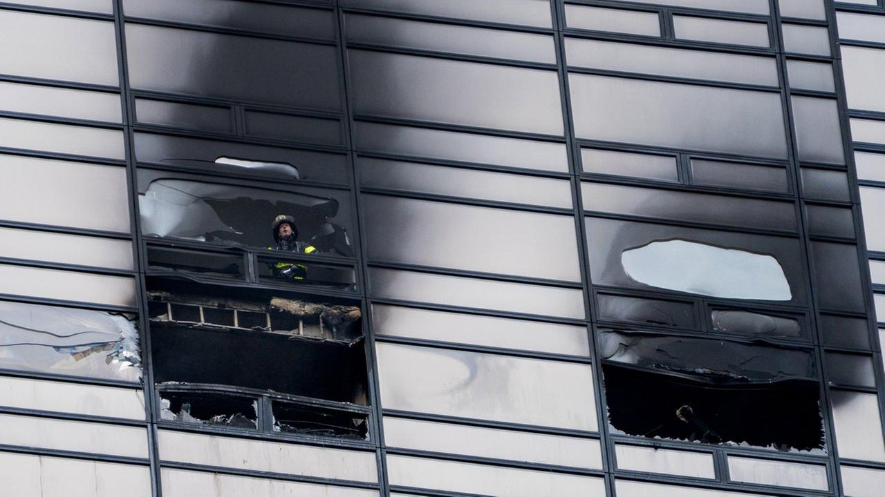 A firefighter looks out from the window of a damaged apartment in Trump Tower in New York on Saturday, April 7.