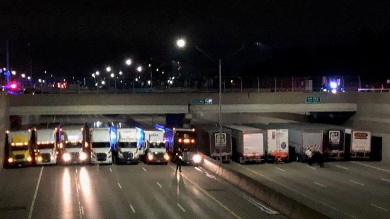 More than a dozen tractor-trailers lined up beneath a Detroit-area freeway overpass to aid police trying to help a man contemplating suicide.