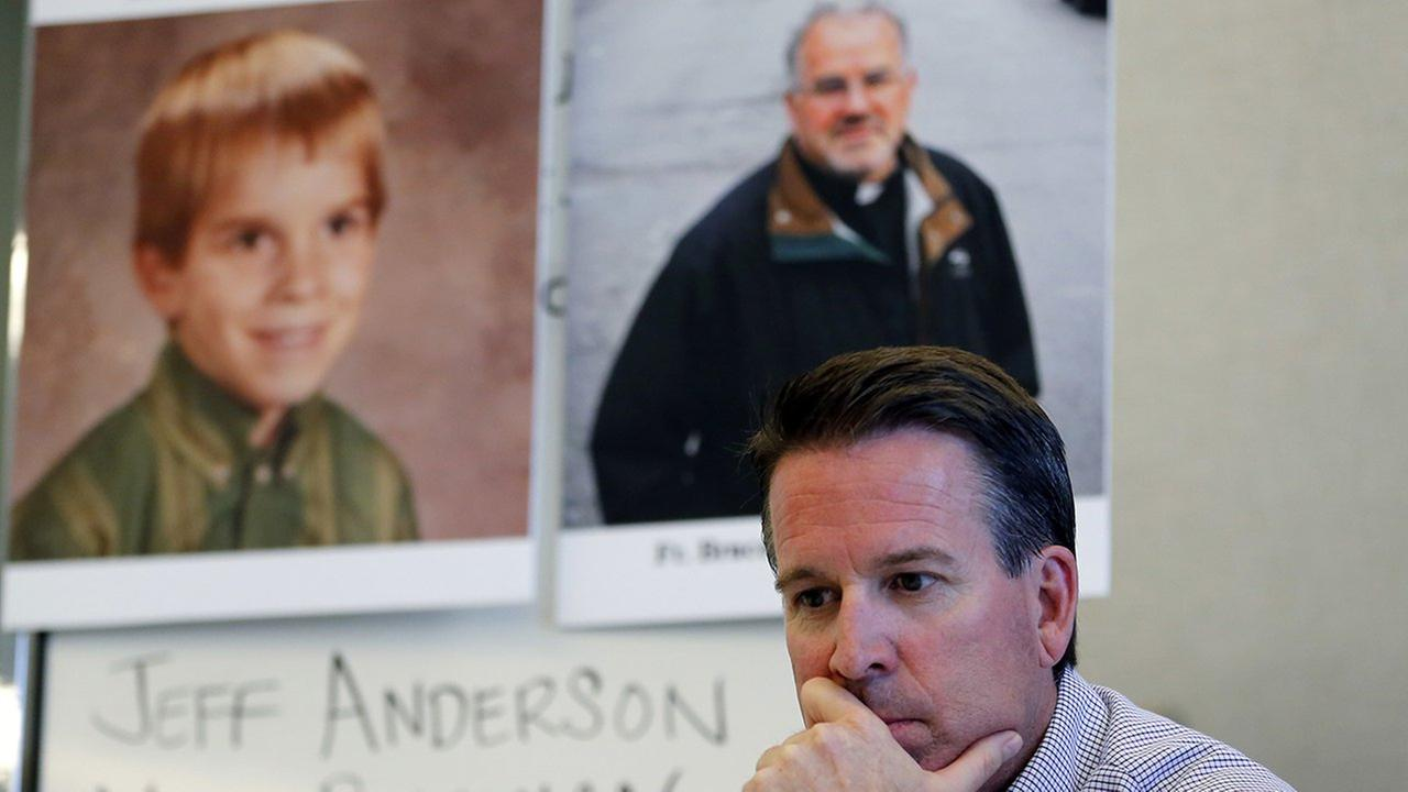 Eric Johnson listens as his attorney speaks during a news conference in front of his childhood portrait and Father Bruce Wellems portrait at Perlmans office, Sept. 26, 2016