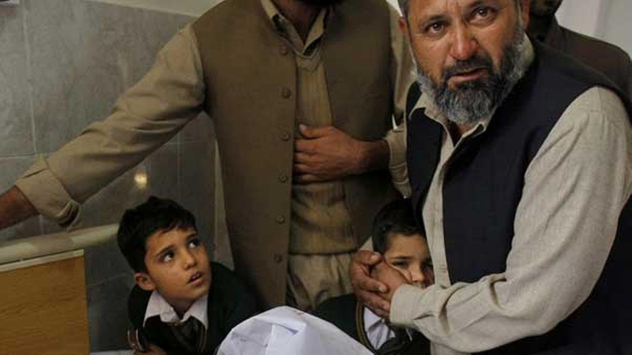 A Pakistani man comforts a student standing at the bedside of a boy who was injured in a Taliban attack on a school, at a local hospital in Peshawar, Pakistan.