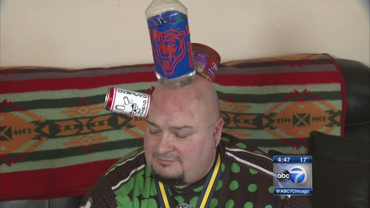 Man makes living stacking inanimate objects on his head