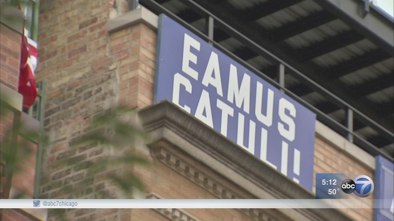 What is the meaning behind Eamus Catuli sign hanging outside Wrigley Field?