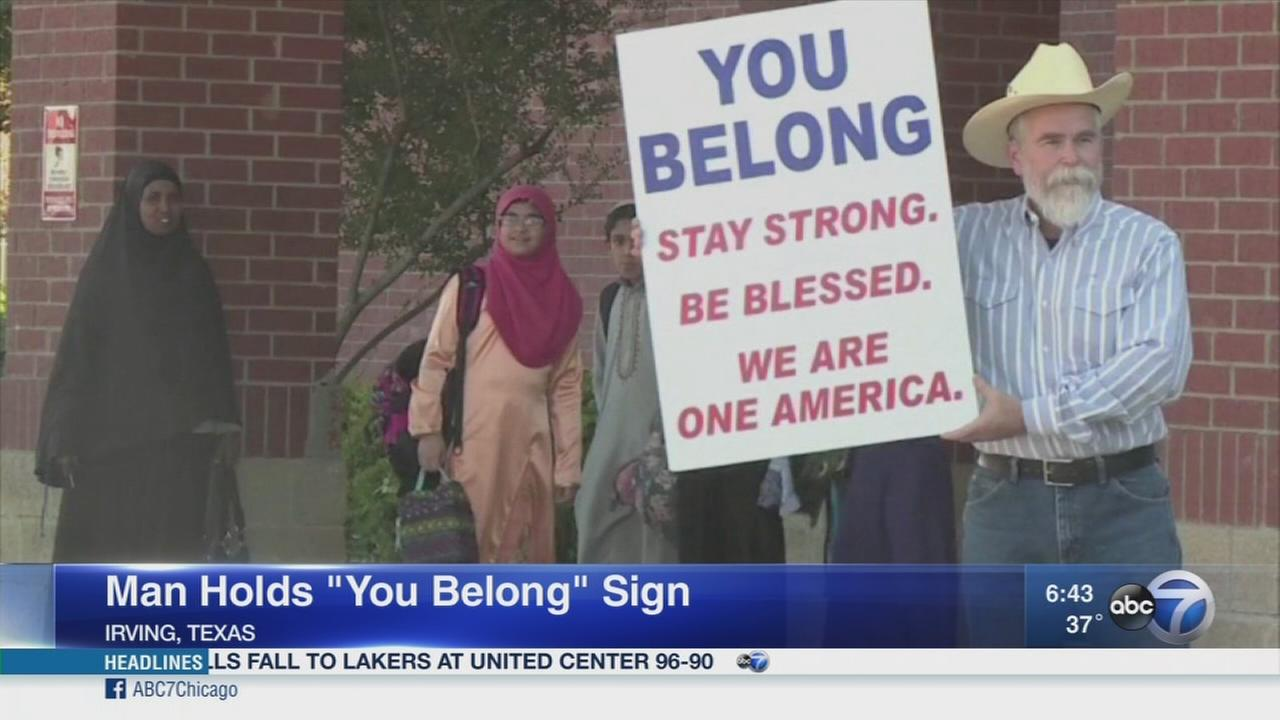 Man holds You Belong sign outside mosque