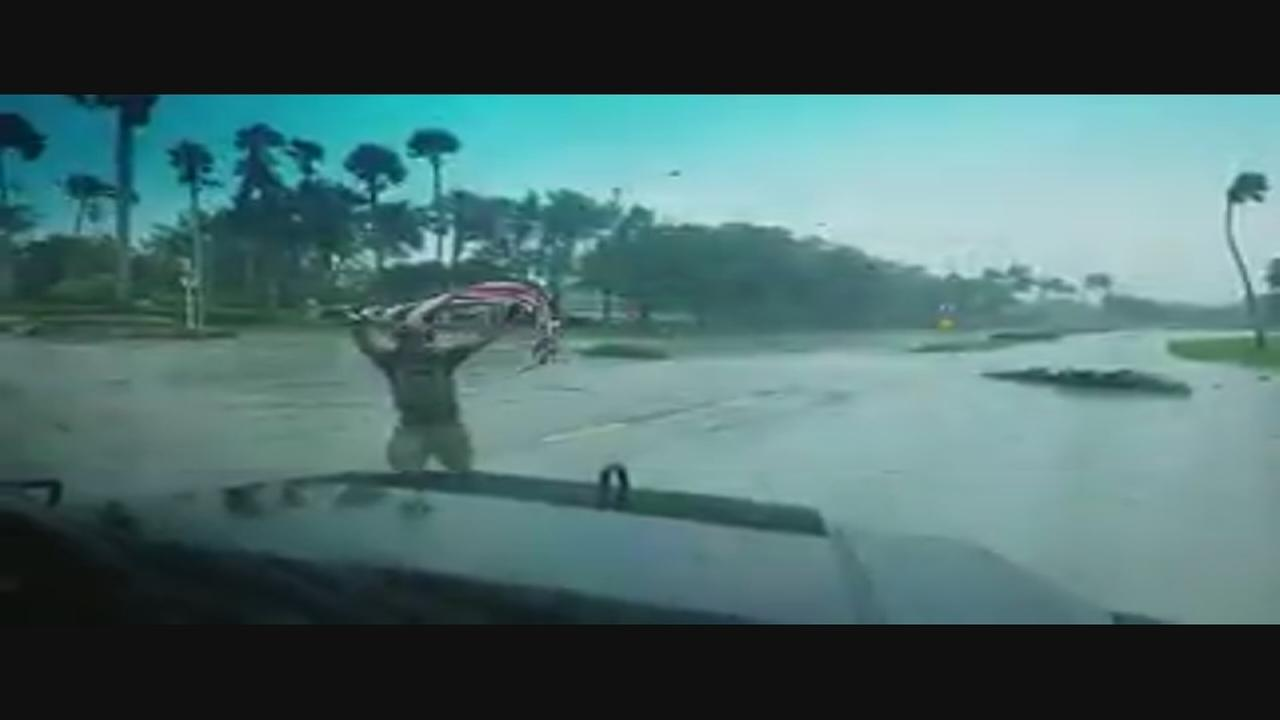 Officer picks up American flag from highway after Irma