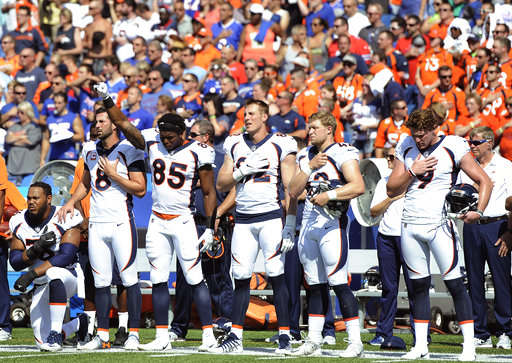 <div class='meta'><div class='origin-logo' data-origin='AP'></div><span class='caption-text' data-credit='AP Photo/Adrian Kraus'>Denver Broncos tight end Virgil Green (85) gestures as teammate Max Garcia, left, takes a knee during the national anthem prior to an NFL game against the Buffalo Bills.</span></div>