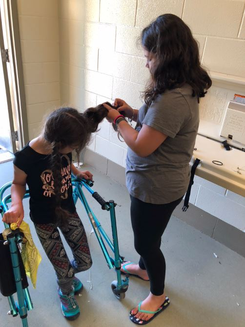 <div class='meta'><div class='origin-logo' data-origin='none'></div><span class='caption-text' data-credit='Helma Wardenaar'>Maggie's friend helps braid her hair on the 4th grade camping trip.</span></div>