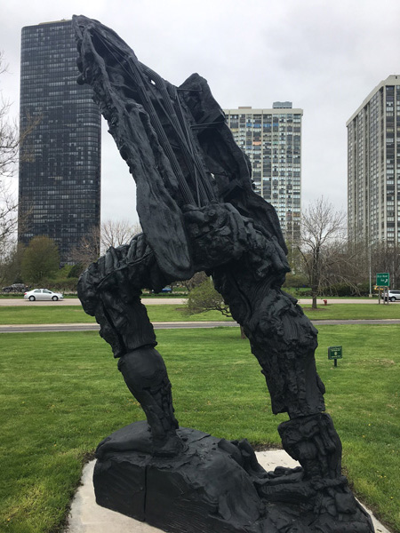 "<div class=""meta image-caption""><div class=""origin-logo origin-image wls""><span>WLS</span></div><span class=""caption-text"">The skeleton-like figure looms over a grassy hill between the beach and the lakeshore path just  north of Foster Avenue Beach in Chicago.</span></div>"