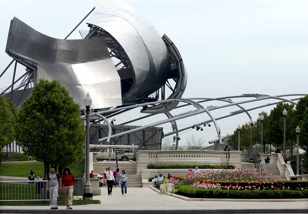 Pedestrians pass the music pavilion, topped with curved stainless steel panels resembling petals of flowers, Thursday, May 6, 2004, at Chicago's Millennium Park. <span class=meta>AP Photo/M. Spencer Green</span>