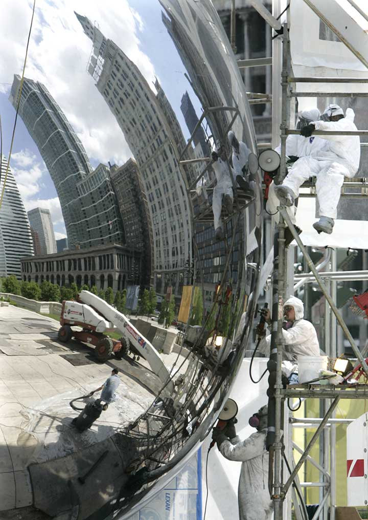 On May 26, 2005, workers are seen buffing the seams of the stainless steel sculpture, which took longer than expected. <span class=meta>AP Photo/Charles Rex Arbogast</span>