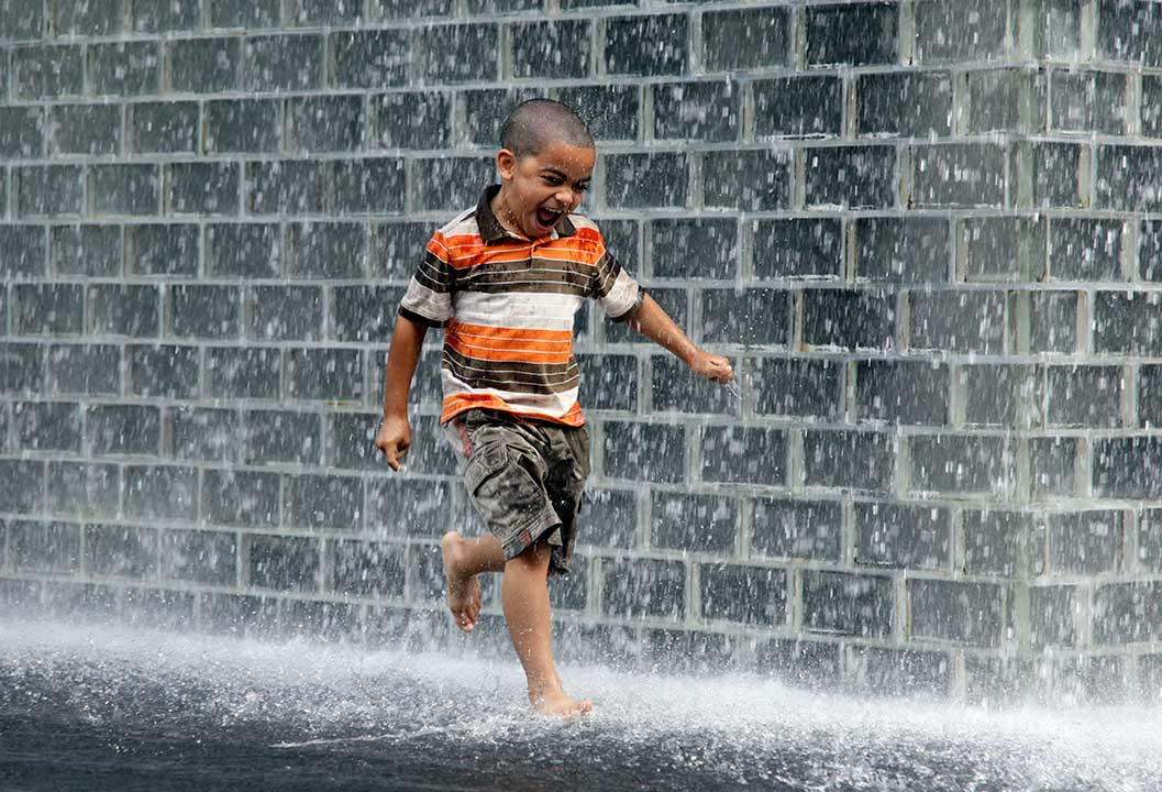 A boy cools off as he runs past the Millennium Park fountain in Chicago, Sunday, July 3, 2011. <span class=meta>AP Photo/Nam Y. Huh</span>