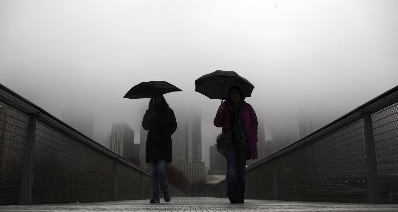 Fog descends upon Millennium Park as pedestrians walk up the bridge from the park to the Chicago Art Institute, Friday, Dec. 30, 2011, in Chicago. <span class=meta>AP Photo/Charles Rex Arbogast</span>