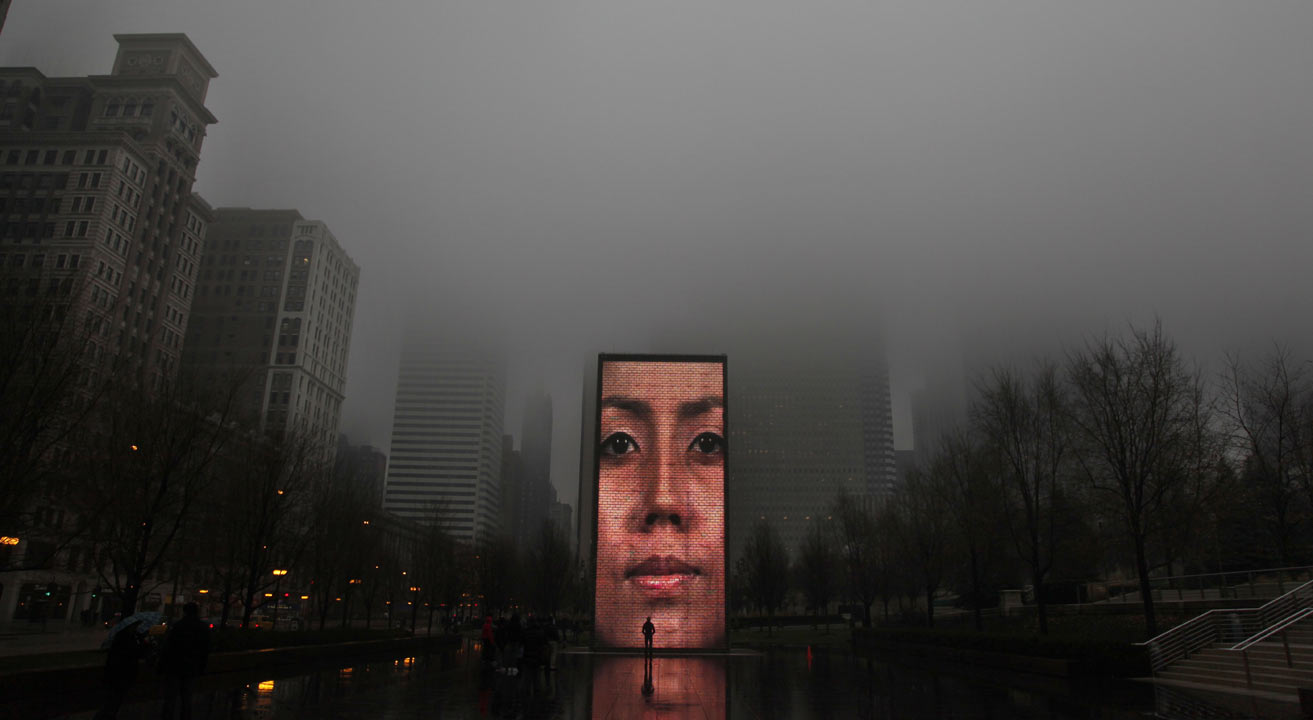 Fog descends upon Millennium Park as a lone pedestrian walks in front of a monolith projection at Crown Fountain, Friday, Dec. 30, 2011, in Chicago. <span class=meta>AP Photo/Charles Rex Arbogast</span>