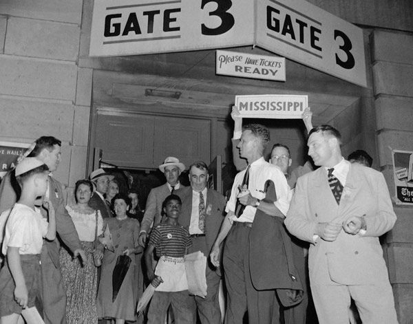 """<div class=""""meta image-caption""""><div class=""""origin-logo origin-image none""""><span>none</span></div><span class=""""caption-text"""">Members of the Mississippi walkout delegation gather under state banners outside Convention Hall after bolting Democratic National Convention in Philadelphia, July 14, 1948.  (AP Photo)</span></div>"""