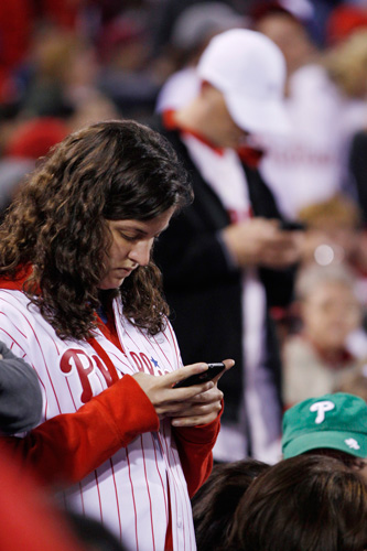 <div class='meta'><div class='origin-logo' data-origin='none'></div><span class='caption-text' data-credit=''>Fans check their cell phones during a baseball game between the Philadelphia Phillies and the New York Mets, Sunday, May 1, 2011, in Philadelphia.</span></div>