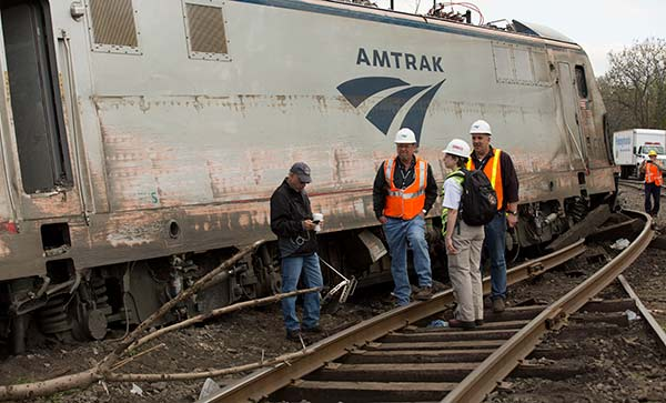 <div class='meta'><div class='origin-logo' data-origin='none'></div><span class='caption-text' data-credit='National Transportation Safety Board'>NTSB Recorder Specialist Cassandra Johnson works with officials on the scene of the Amtrak Train #188 Derailment in Philadelphia, PA</span></div>